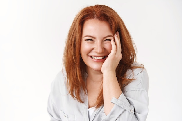 Cheerful good-looking redhead mature woman carefree not care aging taking care skin no wrinkles touch cheek pleased laughing joyfully enjoy squinting happily standing white wall
