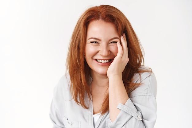 쾌활하고 잘 생긴 빨간 머리 성숙한 여성 근심 걱정 없는 노화 관리 피부 주름이 만지지 않는 뺨 기쁘게 웃고 즐겁게 곁눈질 즐겁게 서 있는 흰 벽