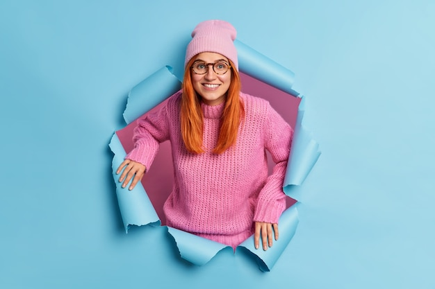 Cheerful good looking woman smiles broadly has red hair dressed in casual clothes has happy mood hears excellent news breaks through blue paper. joyful ginger millennial girl indoor