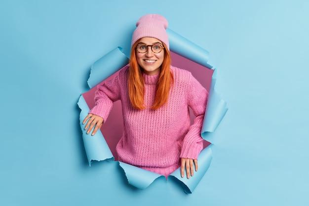 Веселая, симпатичная женщина широко улыбается, имеет рыжие волосы, одетую в повседневную одежду, имеет счастливое настроение, слышит отличные новости, прорывающиеся через синюю бумагу. радостная рыжая миллениальная девушка в помещении