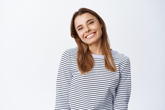 쾌활하고 잘 생긴 여성은 머리를 기울이고 친근한 앞에서 미소 짓고 즐겁고 평온해 보이며 흰 벽에 평상복을 입고 서 있습니다