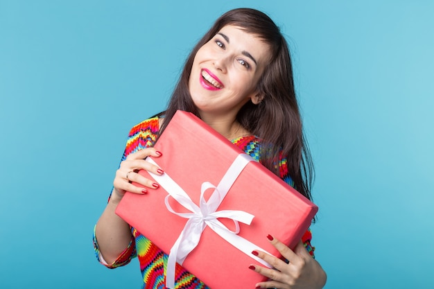 Cheerful good looking young brunette woman holding a red gift box in her hands, but against a blue