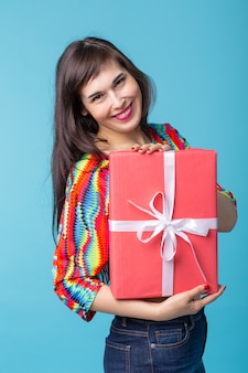 Cheerful good looking young brunette woman holding a red gift box in her hands