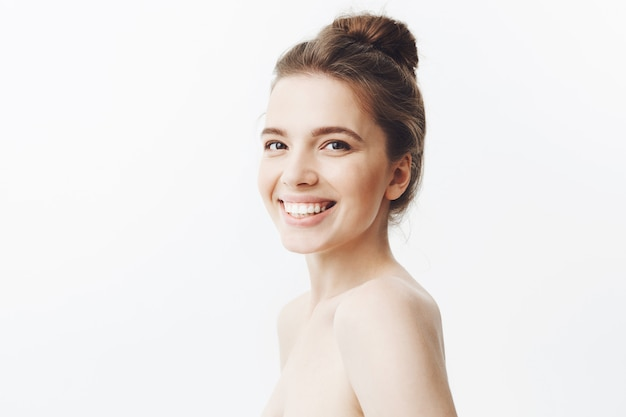 Cheerful good-looking young caucasian woman with dark long hair in bun hairstyle and naked shoulders smiling with teeth with happy and relaxed face expression, beeing glad relax in