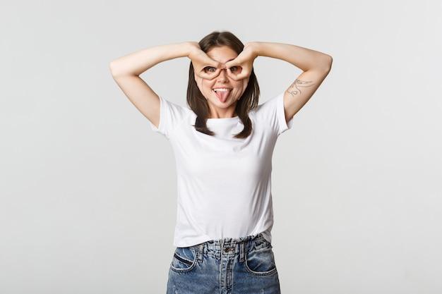 Веселая красивая молодая девушка делает маску супергероя руками над глазами и улыбается счастливым.