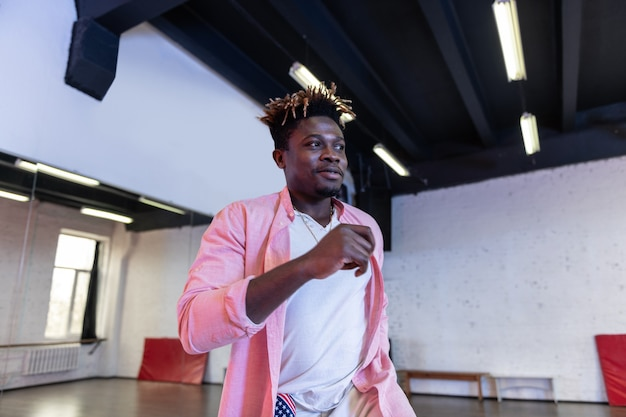 Cheerful good looking young man with short dreadlocks wearing pink shirt while dancing in empty studio