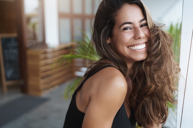 Cheerful good-looking young tanned woman lean on terrace and gazing happily
