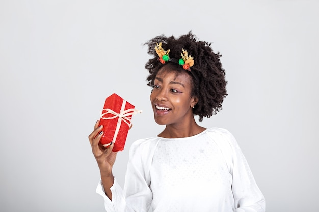 Cheerful good looking young woman holding a red christmas gift box in her hands, against a white background. concept holidays and presents
