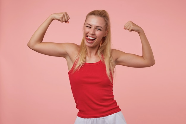 Allegra bella giovane donna con acconciatura casual che mostra le sue mani sportive, sorridendo ampiamente, mostrando la lingua e ammiccando, isolata