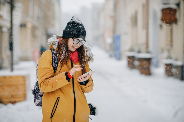 Cheerful gorgeous brunette in winter fashion holding smartphone on urban street