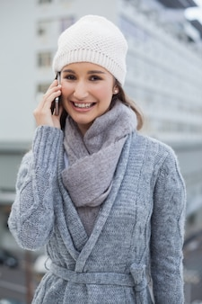 Cheerful gorgeous woman wearing winter clothes having a call