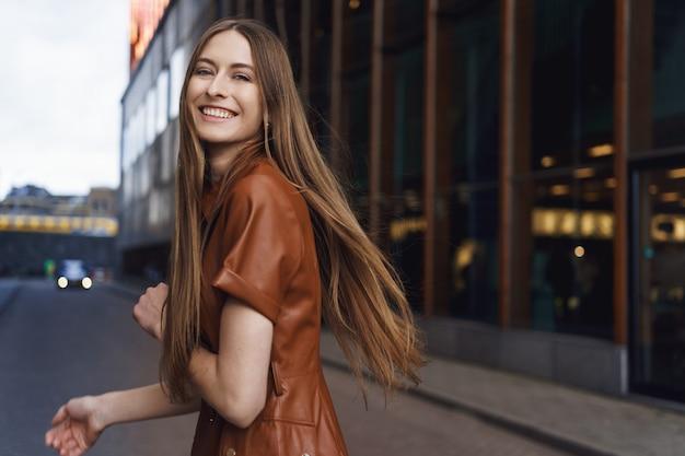 밝고 화려한 젊은 아가씨는 도시의 거리를 걷는 동안 미소를 짓고 카메라를 봅니다.