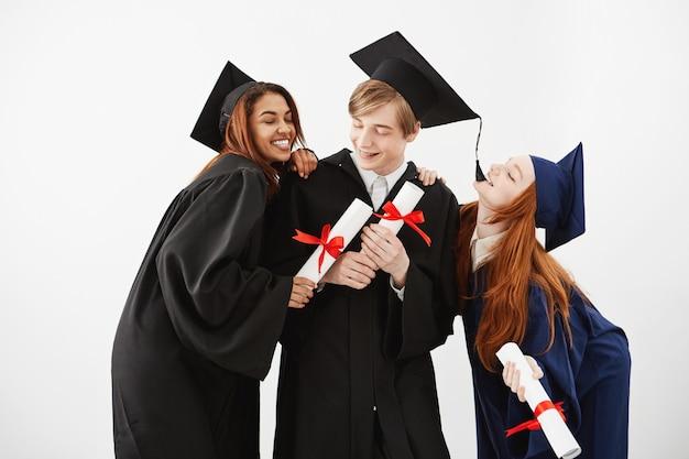 Веселые выпускники одноклассников празднуют улыбающиеся радости.