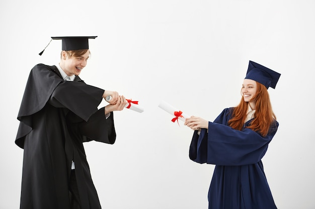 Laureati allegri che sorridono combattendo con i diplomi.