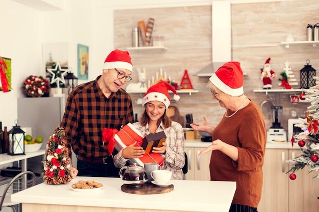 プレゼントを受け取るクリスマスを楽しんでいる陽気な孫