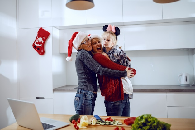 Cheerful grandmother, pregnant woman and little girl hugging in kitchen. on kitchen counter are vegetables and laptop. quality time for christmas concept.