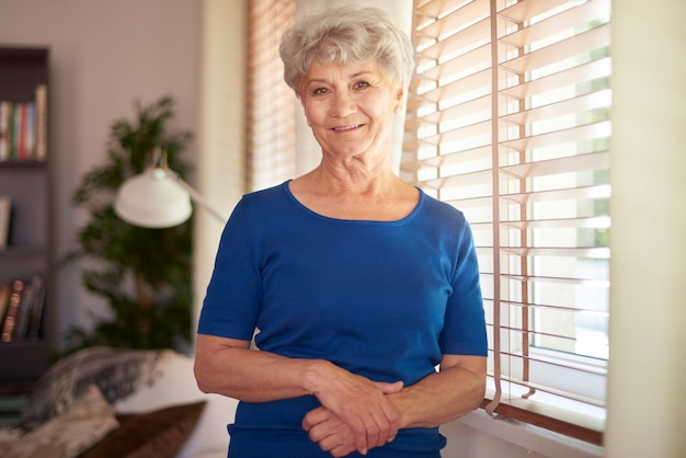 Cheerful grandmother standing next to the window