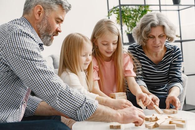 陽気な祖父母と孫が一緒にブロックの木の塔のゲームをしている。リビング ルームのインテリア。