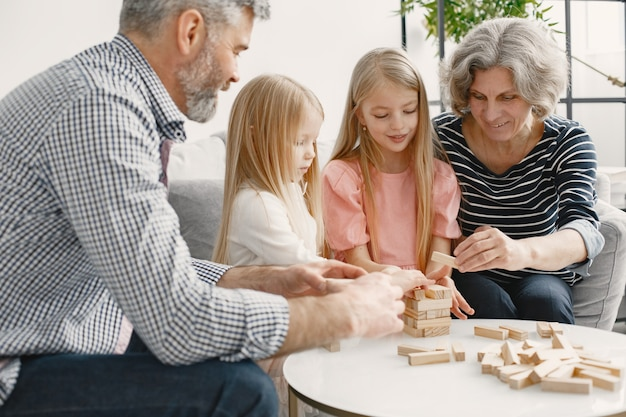 Cheerful grandparents and grandchildren playing blocks wood tower game together. living room interior.