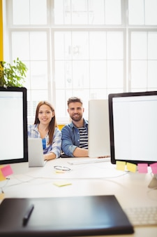 Cheerful graphic designers sitting at desk