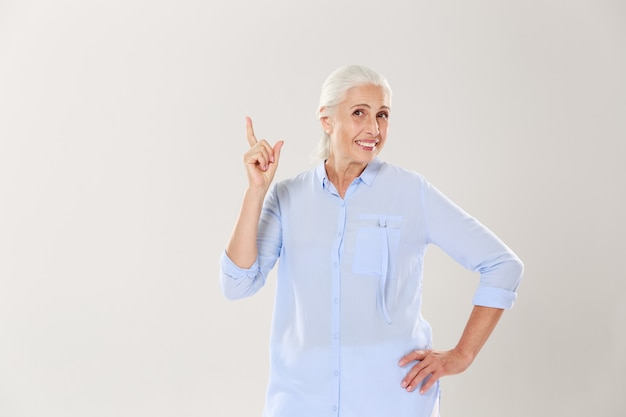Cheerful gray-haired old lady in blue shirt, pointing with finger upward