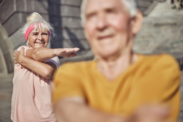 Cheerful gray-haired woman doing a cross-body shoulder stretch behind a man
