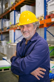 Cheerful grey haired logistic worker in hardhat and uniform standing at shelves in warehouse with arms folded, looking at camera and smiling. vertical shot. labor and blue collar portrait concept