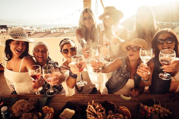 쾌활한 여성 그룹이 함께 즐겁게 지냅니다-집에서 야외에서 레드 와인을 토스트하는 친구-아름다운 여성을위한 축하 파티 이벤트는 많이 웃고 미소 짓습니다.