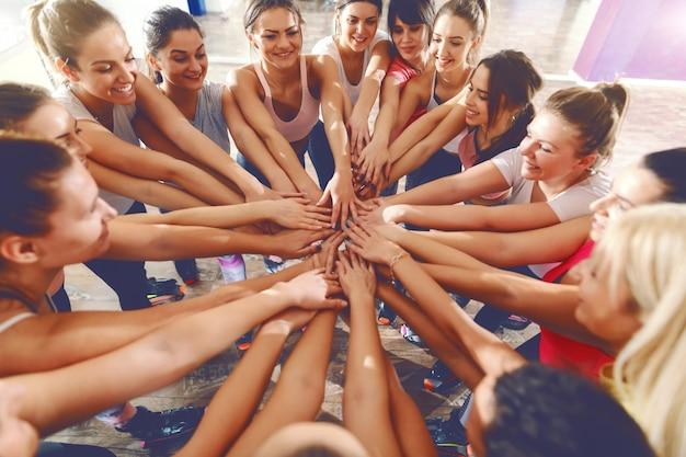 체육관에서 손을 스태킹 맞는 여자의 쾌활 한 그룹. 우리는 함께 무엇이든 할 수 있습니다.