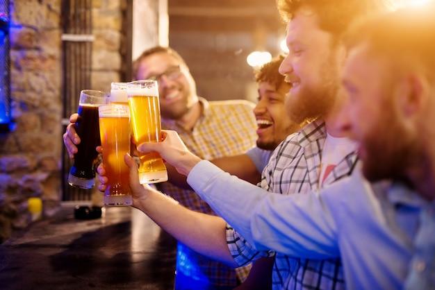 Веселая группа друзей празднует с разливным пивом в баре. фокус вид на пивные бокалы.
