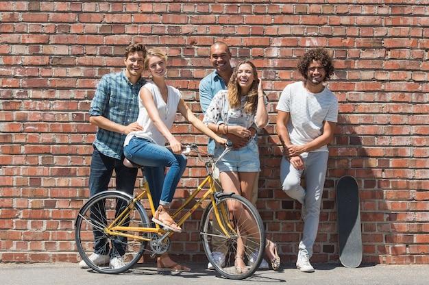 サイクリングやスケートボードで夏休みを楽しんでいる友達の陽気なグループ