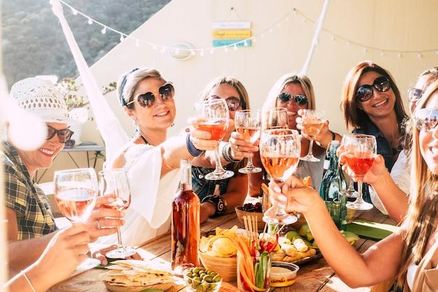 Веселая группа счастливых людей женского пола звонит и тосты вместе с дружбой и счастьем