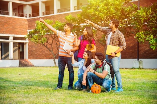 서 또는 대학 캠퍼스에 앉아있는 동안 빈 가리키는 인도 아시아 대학생의 쾌활한 그룹