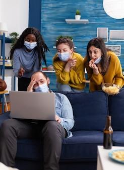 Веселая группа многонациональных друзей, смеющихся вместе, сохраняя социальное дистанцирование и носящих лицевую маску, чтобы предотвратить распространение кооронавируса во время глобальной вспышки, смотрят видео на ноутбуке в гостиной.
