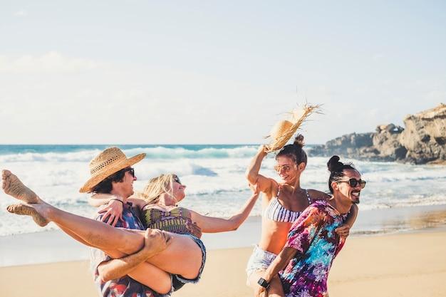 男の子と女の子の陽気なグループは、夏休みの休暇中にビーチで一緒に楽しんでいます