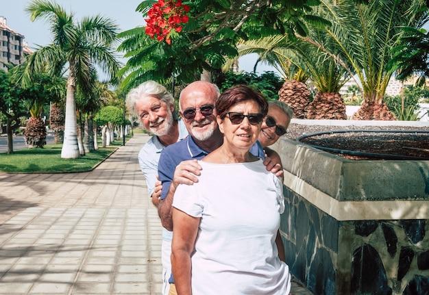 야자나무 아래 은퇴한 4명의 은퇴한 사람들이 공공 공원에서 즐거운 시간을 보내는 쾌활한 고위 친구들