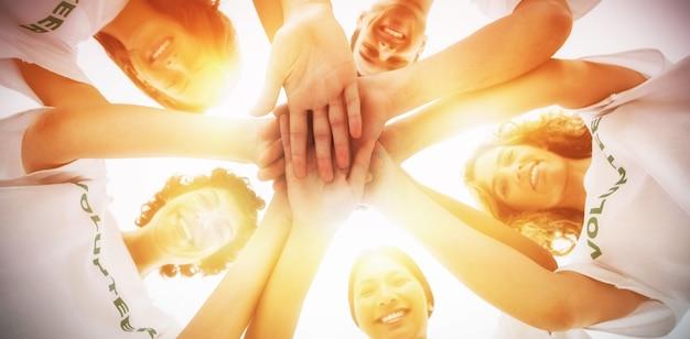 手を組むボランティアの陽気なグループ