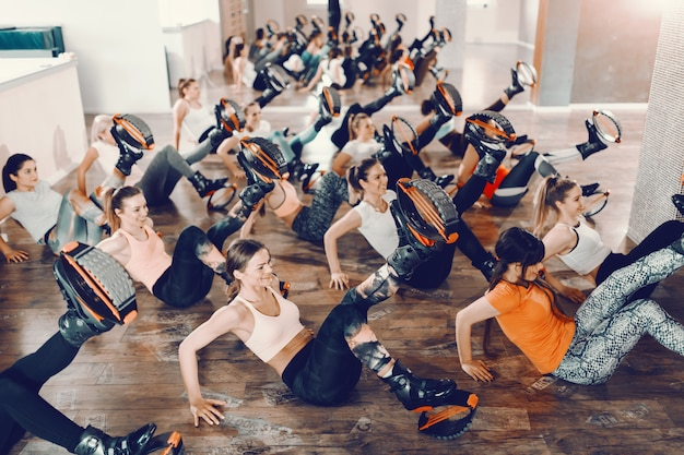Cheerful group of women sitting on the floor and doing kicks with kangoo jumps footwear. gym interior.