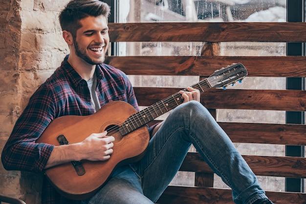陽気なギタリスト。ギターを弾き、窓辺に座って笑っている陽気なハンサムな若い男