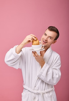 Cheerful guy can't resist lest he eat croissant