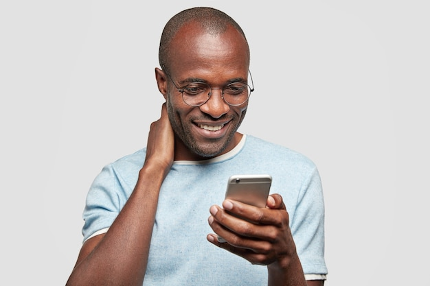 Cheerful guy chats on smart phone with friend or girlfriend, recieves good news in message, holds modern cell phone