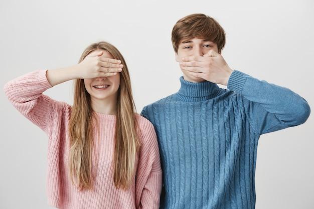 陽気な男は口を閉じて、目を閉じて笑っているブロンドの女の子