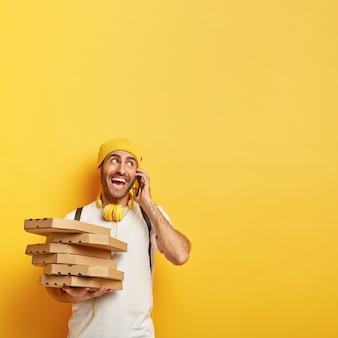 陽気な男はレストランからピザの箱を配達し、スマートフォンを介してクライアントに電話をかけ、喜んで脇に見え、カジュアルな服を着て、黄色い壁に向かってポーズをとります。食料の配達と宅配便の仕事