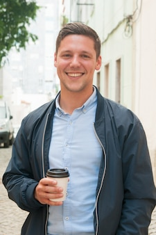 Cheerful guy enjoying outdoor coffee break