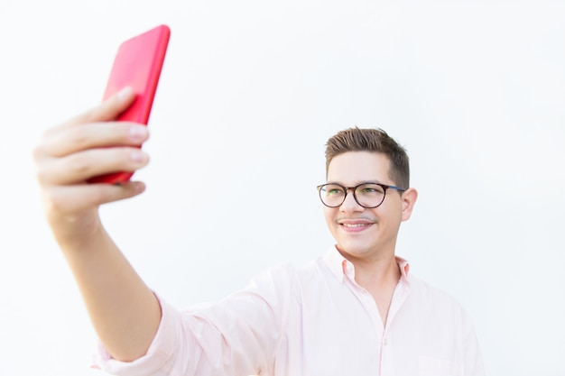 Cheerful guy in eyeglasses holding red mobile phone