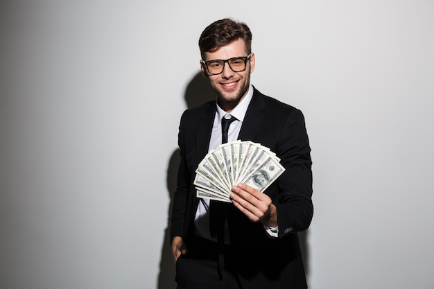 Cheerful guy in formal wear showing bunch of money