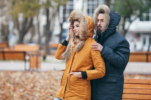 A cheerful guy and a girl are walking in the autumn park