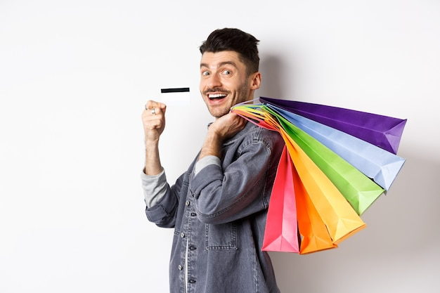 Cheerful guy going on shopping with credit card, holding bags on shoulder and smiling excited at camera, white background.