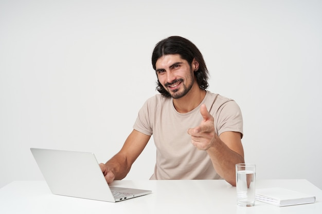 Cheerful guy, happy businessman with black hair and beard. office concept. sitting in work place. working on laptop, isolated over white wall