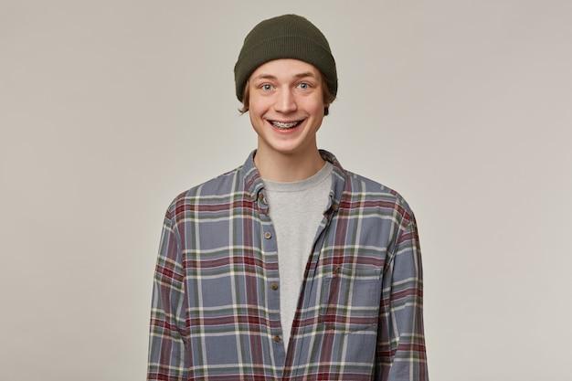 쾌활 한 남자, 금발 머리를 가진 행복 찾는 남자. 체크 무늬 셔츠와 비니 착용. 중괄호가 있습니다. 사람과 감정 개념. 회색 벽에 고립 된 긍정적 인보고